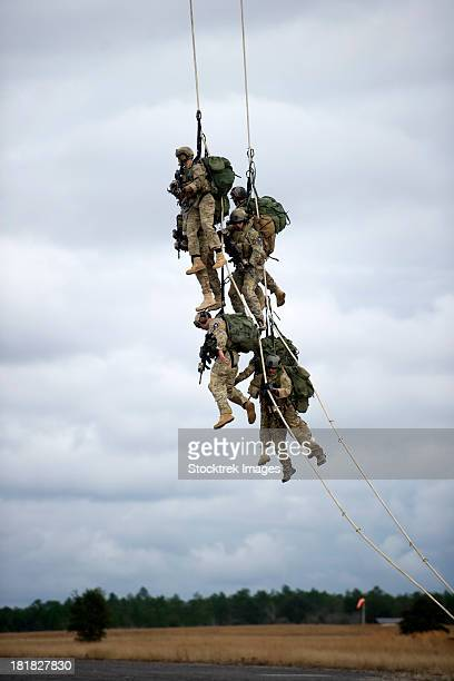 U.S. Soldiers are lifted off the ground by a CH-47 Chinook helicopter.