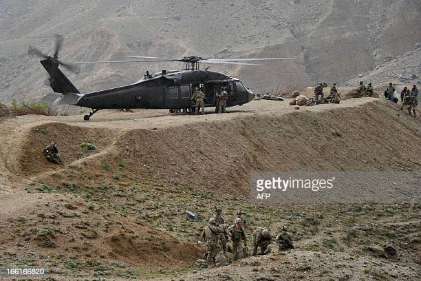 US soldiers are pictured near a UH60 Black Hawk helicopter near the scene of a helicopter crash during a recovery operation in the Pachir Wa Agam...