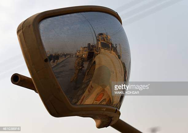 US soldiers are reflected in a rear view mirror at the scene with a damaged car following a suicide car bomb attack on a European Union police...