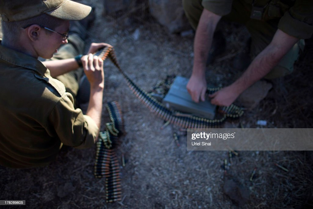 Soldiers arm their tanks as Israeli troops start preparations at a deployment area during a military exercise on August 28, 2013 near the border with Syria, in the Israeli-annexed Golan Heights. Tension is rising in Israel amid talks of an international military intervention In Syria following reported chemical weapons attacks.