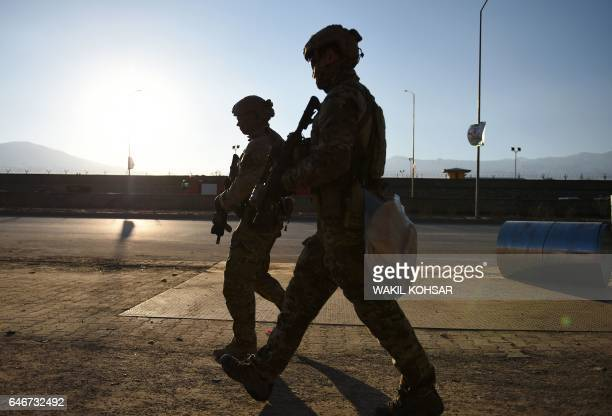 US soldiers arrive at the site of a suicide car bombing that targeted an Afghan police district headquarters building as a gun battle continues...