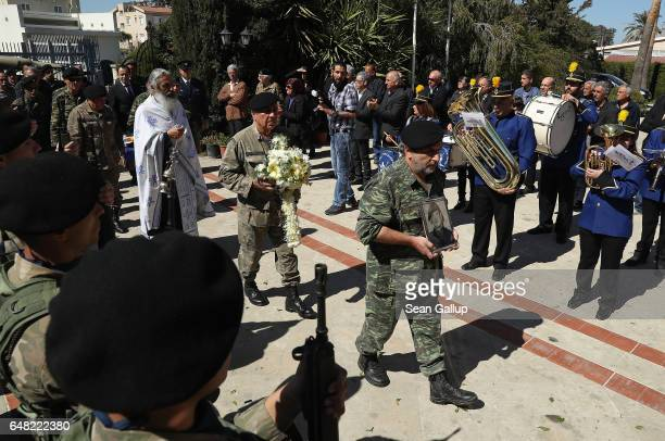 Soldiers arrive carrying a portait and a coffin that contains the remains of Georgiou Theodoulos Theodoulou at his Orthodox funeral service on March...