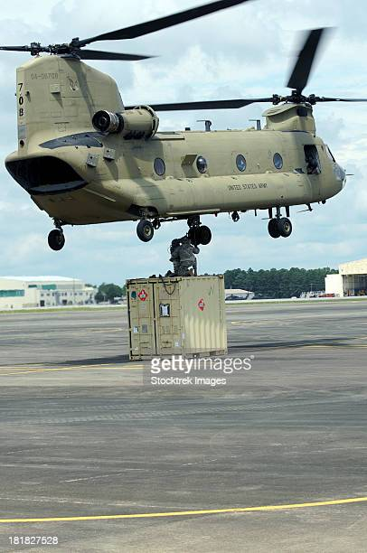 Soldiers attach a container to a CH-47F Chinook slingload hook.