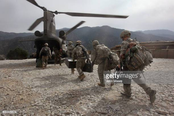 S soldiers board an Army Chinook transport helicopter after it brought fresh soldiers and supplies to the Korengal Outpost on October 27 2008 in the...