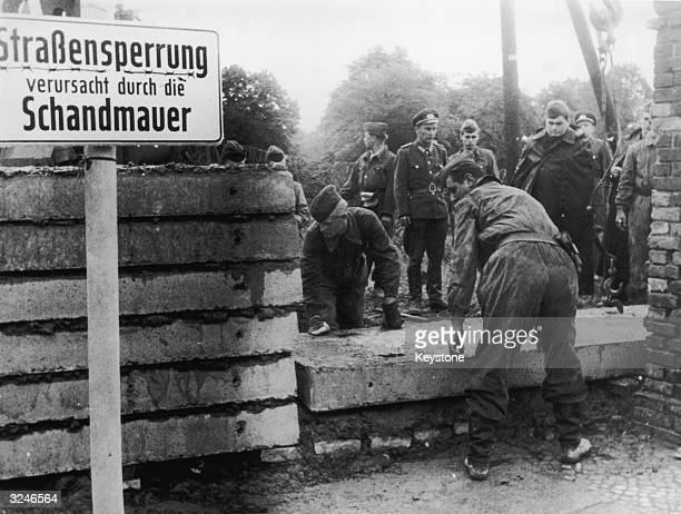 Soldiers building the Berlin Wall as instructed by the East German authorities in order to strengthen the existing barriers dividing East and West...