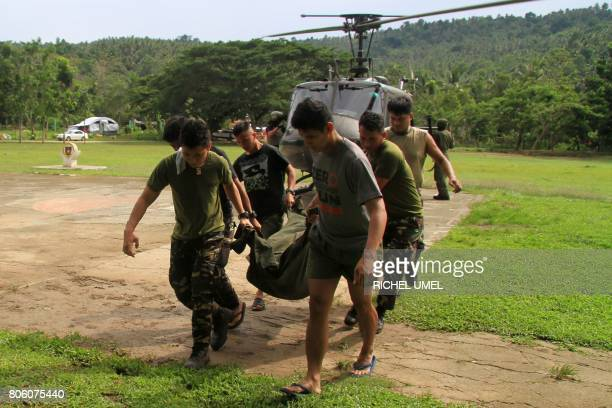 Soldiers carry a body bag containing the body of a colleague killed in action during fighting between government troops and Islamist militants in...