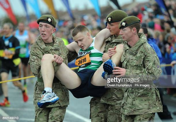 Soldiers carry a competitor during the 2013 Great North Run between Newcastle and South Sheilds