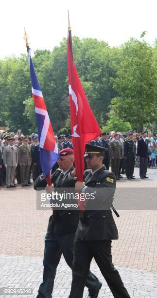 Soldiers carry a Turkish flag and a British flag during the 50th Foundation Anniversary of the North Atlantic Treaty Organization Base in Brunssum...
