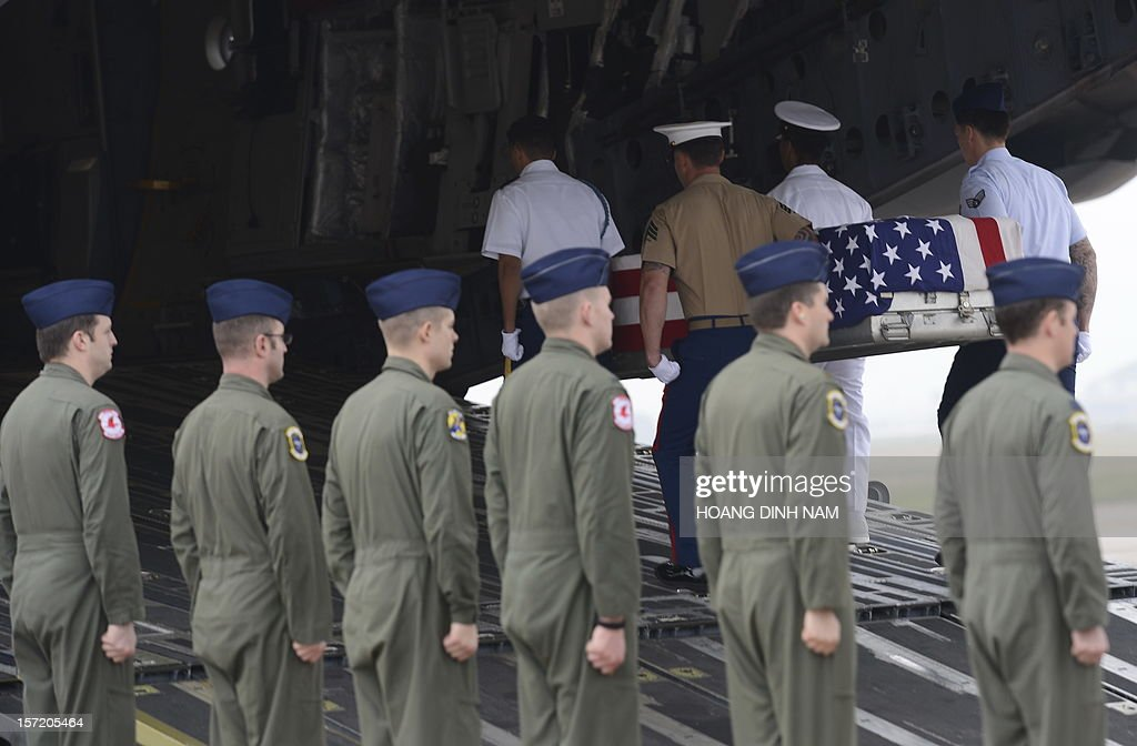 US soldiers carry a US flag draped casket containing what is believed to be remains of a US service man listed as missing in action during the Vietnam war into a US Airforce aircraft at a MIA (missing in action) repatriation ceremony held at Hanoi's Noi Bai airport on November 30, 2012. The three remains which were repatriated at this 125th post-war repatriation of US remains from Vietnam were recovered by recent joint MIA research conducted by Vietnamese and US field teams. To date 985 US soldiers from the Vietnam War have been identified since 1973 - 689 from Vietnam, 258 from Laos, 35 from Cambodia and three from China, according to a press release from the US embassy in Hanoi. Some 1,661 US soldiers are still unaccounted for from the war, including 1,282 in Vietnam, according to the press release. AFP PHOTO / HOANG DINH Nam