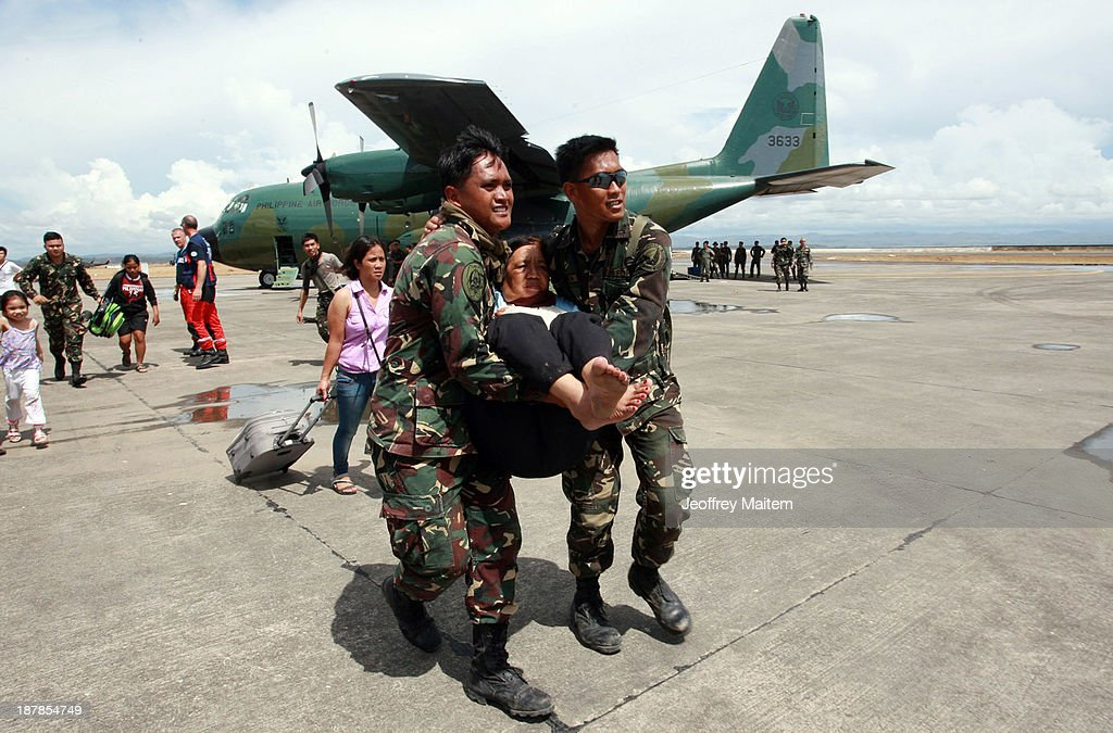 Soldiers carry an elderly woman as US marines prepare relief for people affected in the aftermath of Typhoon Haiyan on November 13, 2013 in Tacloban, Leyte, Philippines. Typhoon Haiyan, packing maximum sustained winds of 195 mph (315 kph), slammed into the southern Philippines and left a trail of destruction in multiple provinces, forcing hundreds of thousands to evacuate and making travel by air and land to hard-hit provinces difficult. Around 10,000 people are feared dead in the strongest typhoon to hit the Philippines this year.