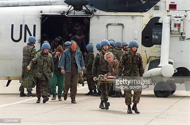 UN soldiers carry an injured man on a stretcher upon their arrival by helicopter at Tuzla airport 25 April 1993 as part of evacuation operations of...