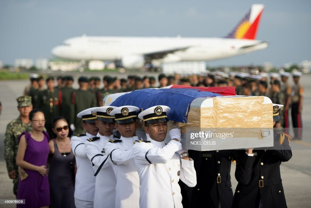Soldiers carry one of the five flag draped coffin of soldiers that arrived at the Villamor Airbase in Manila on June 21, 2014. Ten Muslim extremists and seven soldiers were killed in one of the bloodiest clashes in the southern Philippines in recent months, the military said. AFP PHOTO/NOEL CELIS