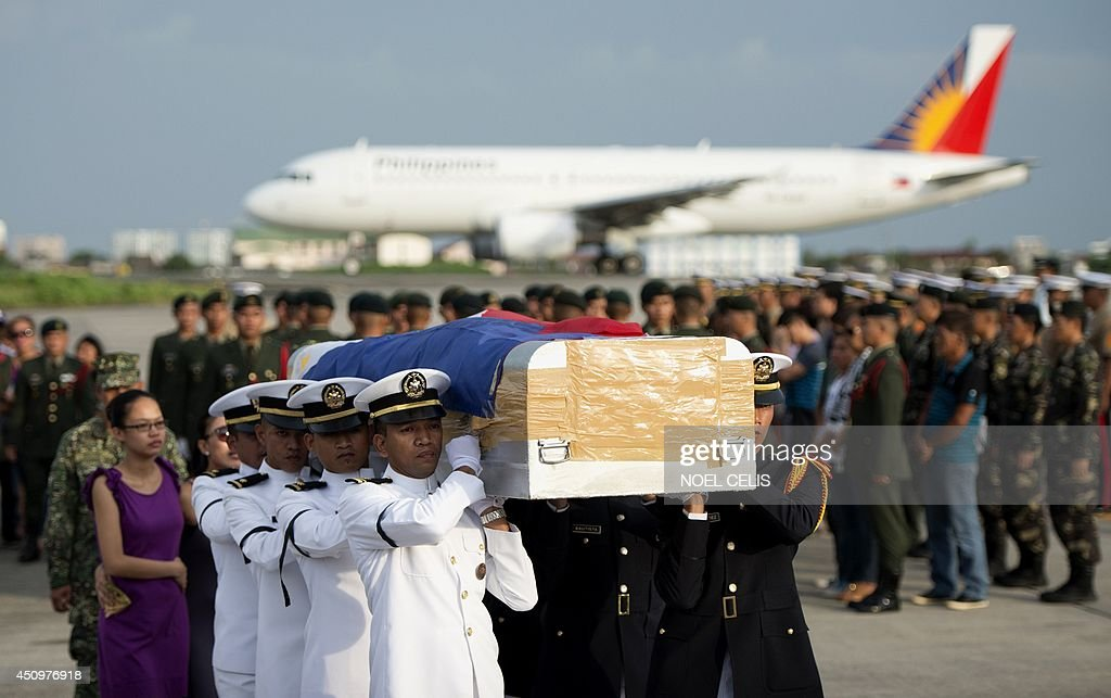 Soldiers carry one of the five flag draped coffins that arrived the Villamor Airbase in Manila on June 21, 2014. Ten Muslim extremists and seven soldiers were killed in one of the bloodiest clashes in the southern Philippines in recent months, the military said.