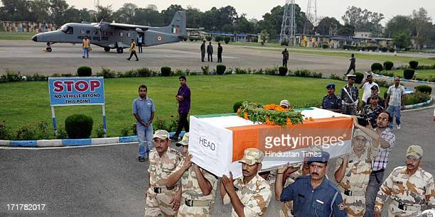ITBP soldiers carry the body of martyr ITBP Inspector Bhim Singh whose body was flown in from Uttarakhand at Jammu Technical Airport on June 28 2013...