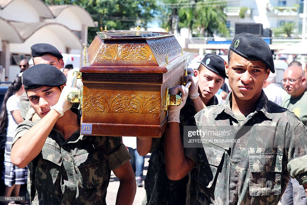 Soldiers carry the coffin of a victim of a nightclub blaze in Santa Maria, 550 Km from Porto Alegre, southern Brazil on January 28, 2013, where more than 230 people died and 116 more were injured. Shocked survivors, mostly science students in Santa Maria, described how scores of revelers were trampled to death or succumbed to smoke inhalation as blocked exits and rising flames caused panic AFP PHOTO / Jefferson BERNARDES