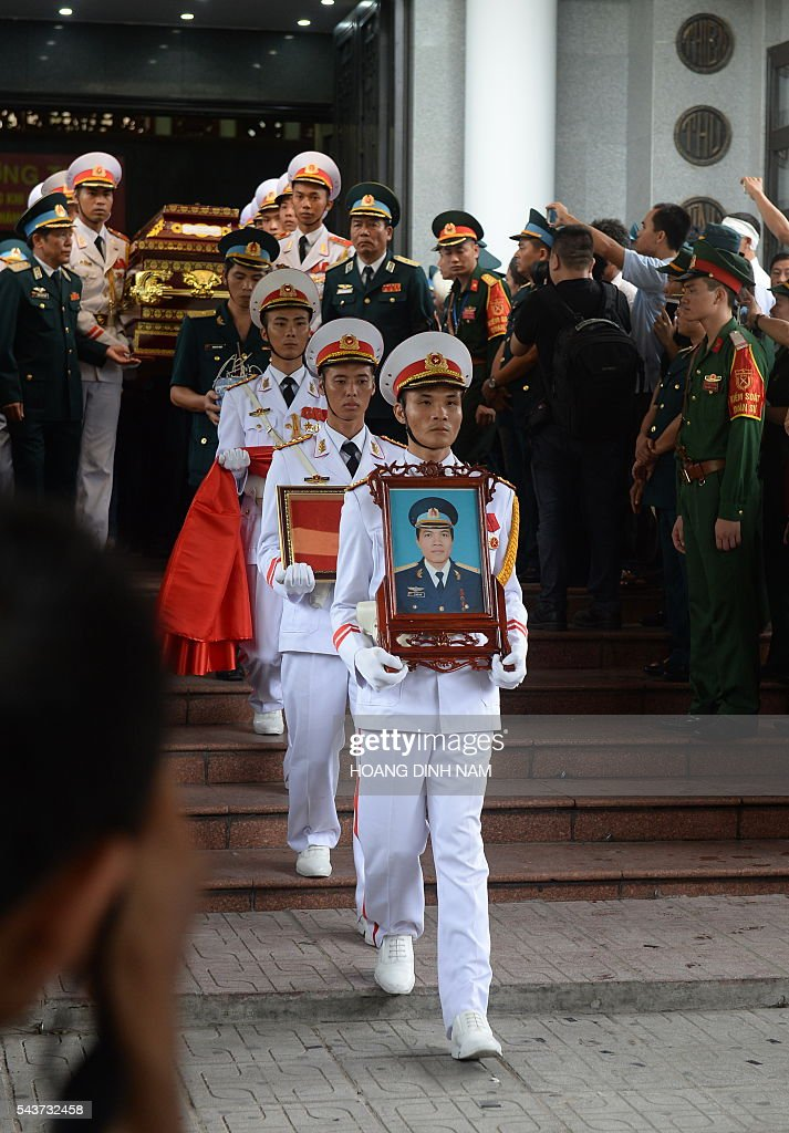 Soldiers carry the coffin of one of the victims of a rescue aircraft that crashed on June 16, 2016 over the South China Sea during a search mission for a Vietnamese Airforce Sukhoi SU-30MK2 that went missing two days earlier, during an official funeral ceremony in Hanoi on June 30, 2016. / AFP / HOANG