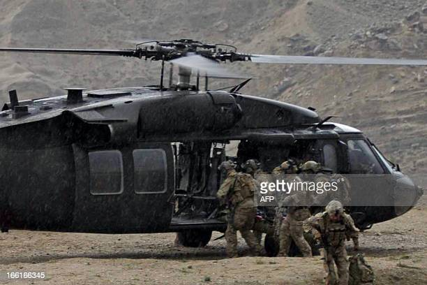 US soldiers carry the remains of a fallen comrade into a UH60 Black Hawk helicopter near the scene of a helicopter crash in the Pachir Wa Agam...