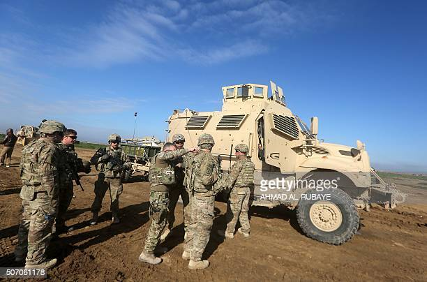 US soldiers chat as they train Iraq's 72nd Brigade in a livefire exercise in Basmaya base southeast of the Iraqi capital Baghdad on January 27 2016...