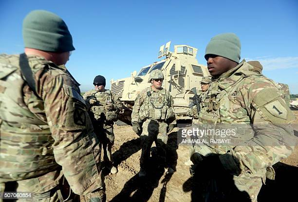 US soldiers chat as they train Iraq's 72nd Brigade taking part in a livefire exercise in Basmaya base southeast of the Iraqi capital Baghdad on...