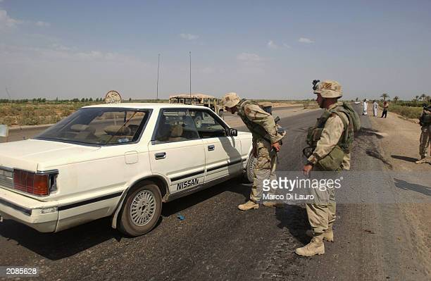 Soldiers check a car and its occupants at a check point on June 16 2003 on the outskirts of Fallujah 70 km south of Baghdad in Iraq US forces are...