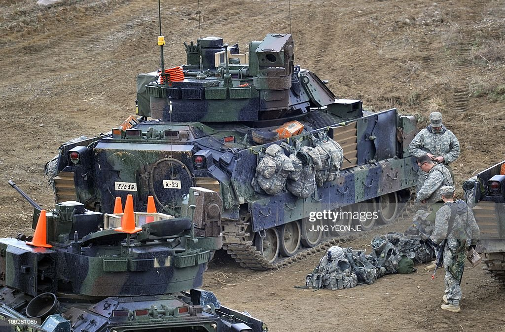 US soldiers check their equipments next to a Bradley armored vehicle at a military training field in the border city of Yeoncheon, northeast of Seoul, on April 11, 2013. The United States has warned North Korea it is skating a 'dangerous line' with an expected missile launch that could start a whole new cycle of escalating tensions in a region already on a hair-trigger.