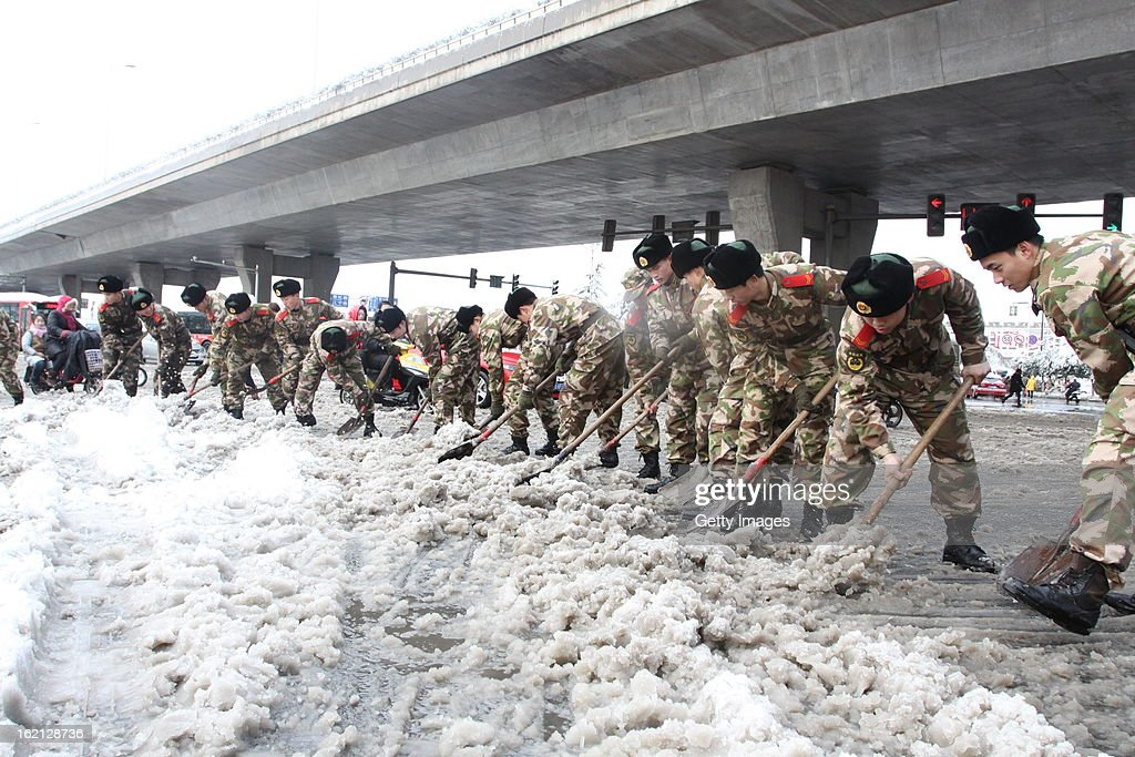 Soldiers clean a snow-covered road on February 19, 2013 in Nanjing, China. Heavy snow hit large areas of east China on Tuesday.
