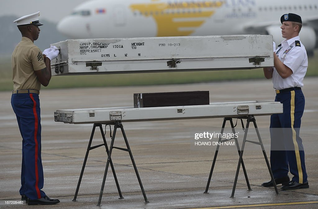 US soldiers close a casket containing what is believed to be remains of a US service man listed as missing in action during the Vietnam war, at a MIA (missing in action) repatriation ceremony held at Hanoi's Noi Bai airport on November 30, 2012. The three remains which were repatriated at this 125th post-war repatriation of US remains from Vietnam were recovered by recent joint MIA research conducted by Vietnamese and US field teams. To date 985 US soldiers from the Vietnam War have been identified since 1973 - 689 from Vietnam, 258 from Laos, 35 from Cambodia and 3 from China, according to a press release from the US embassy in Hanoi. Some 1,661 US soldiers are still unaccounted for from the war, including 1,282 in Vietnam, according to the press release. AFP PHOTO / HOANG DINH Nam
