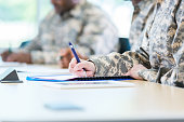 Unrecognizable military soldiers take exam during college class.
