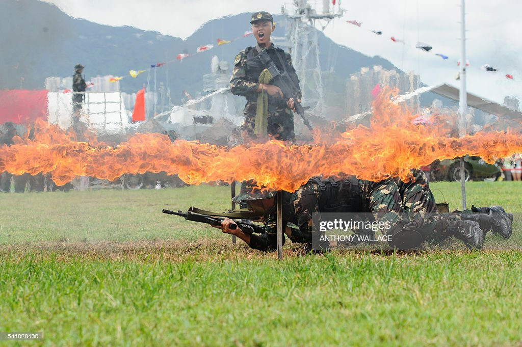 PLA soldiers crawl under a burning frame as their colleague (top C) shouts during a demonstration at the open day of the Chinese People's Liberation Army (PLA) Navy Base at Stonecutter Island in Hong Kong on July 1, 2016, to mark the 19th anniversary of the Hong Kong handover to China. / AFP / Anthony Wallace