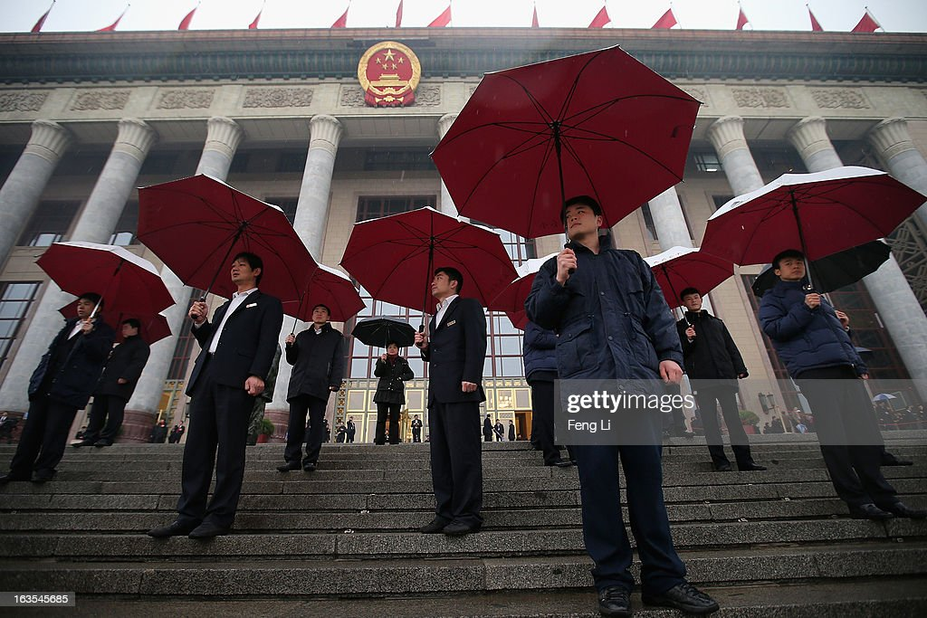 Soldiers dressed as ushers hold umbrellas in the rain at the entrance of the Great Hall of the People as they wait for delegates arrive to the closing session of the annual Chinese People's Political Consultative Conference (CPPCC) on March 12, 2013 in Beijing, China. The newly-elected Chairman of the CPPCC Yu Zhengsheng pledged Tuesday that China will not copy Western political systems under any circumstances.