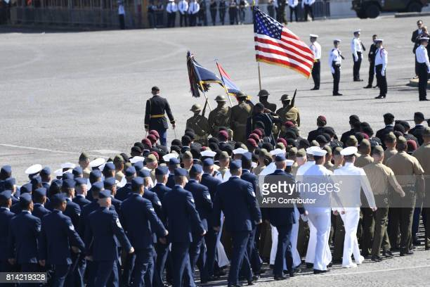 Soldiers dressed as World War I Sammies carry the US flag as they lead US troops marching during the annual Bastille Day military parade on the...