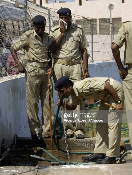 Soldiers drink from the ground hose pipe as England practice at the Sardar Patel Stadium Ahmedabad India