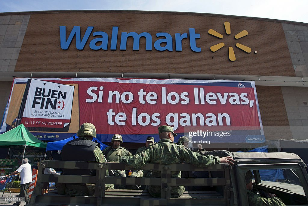 Soldiers drive past a Wal-Mart de Mexico SAB de CV store in Mexico City, Mexico on Saturday, Nov. 17, 2012. El Buen Fin, Mexico's equivalent of Black Friday, when the year's biggest discounts are offered by participating stores, is held on the third weekend of November and will run through Nov. 19. Photographer: Susana Gonzalez/Bloomberg via Getty Images