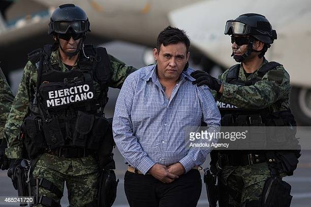 Soldiers escort a man who authorities identified as Omar Trevino Morales alias 'Z42' leader of the criminal group 'Los Zetas' at the Attorney General...