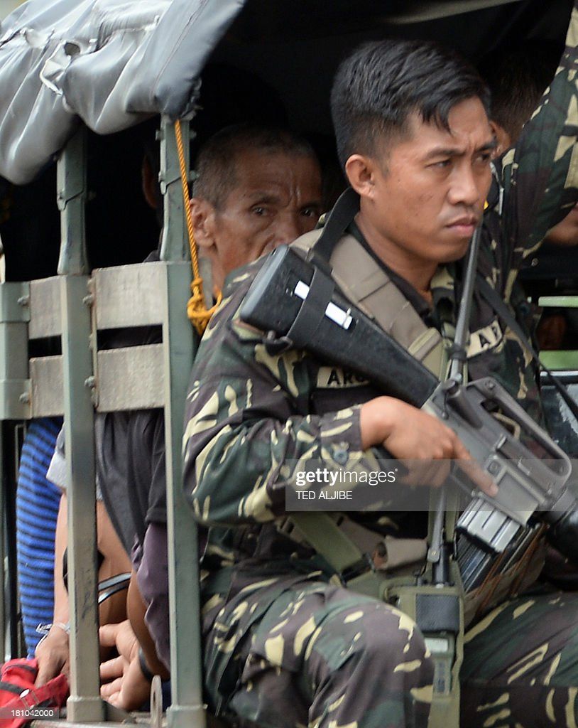 Soldiers escort a military vehicle transporting surrendered Muslim rebels (in civilian clothes) to a police station, as firefight between government troops and remnants of Muslim rebels rages with the stand-off entering its 10th day in the city of Zamboanga on the southern island of Mindanao on September 19, 2013. Philippine soldiers pursued heavily armed Muslim rebels through the streets and homes of a major city September 18, warning they would be killed or captured unless they surrendered.