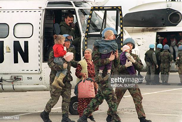 UN soldiers escort refugees from the Serbbesieged Bosnian enclave of Srebrenica upon their arrival by helicopter at Tuzla airport 18 April 1993 More...