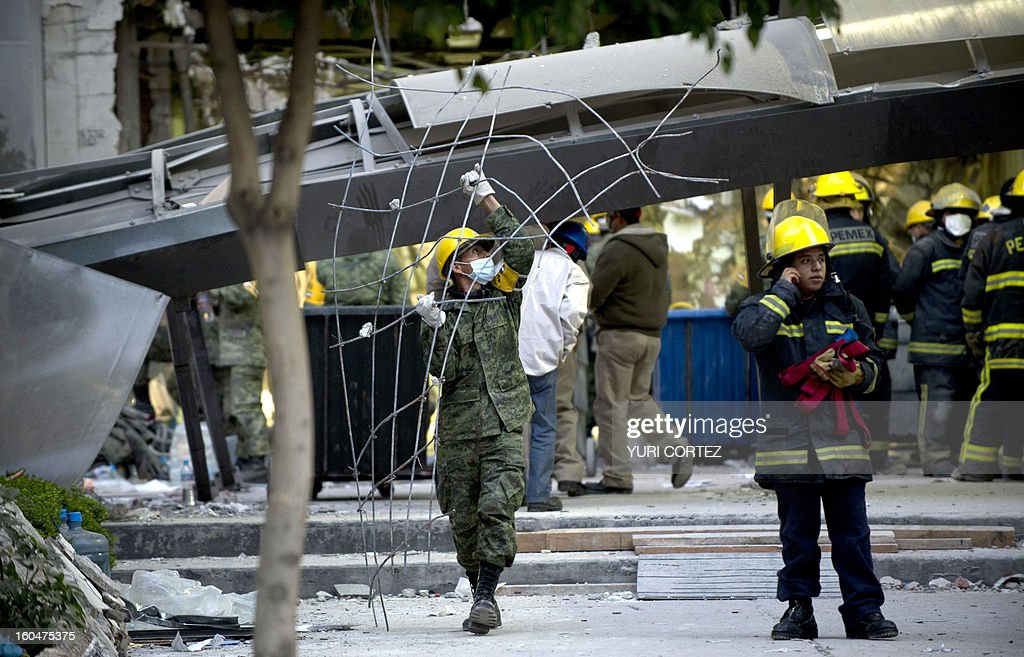 Soldiers, Federal policemen and firefighter remove debris looking for victims of the headquarters of state-owned Mexican oil giant Pemex in Mexico City on February 1, 2013, following a blast inside the building. An explosion rocked the skyscraper, leaving up to now 32 dead and 100 injured, as a plume of black smoke billowed from the 54-floor tower, according to official sources. AFP PHOTO/ YURI CORTEZ