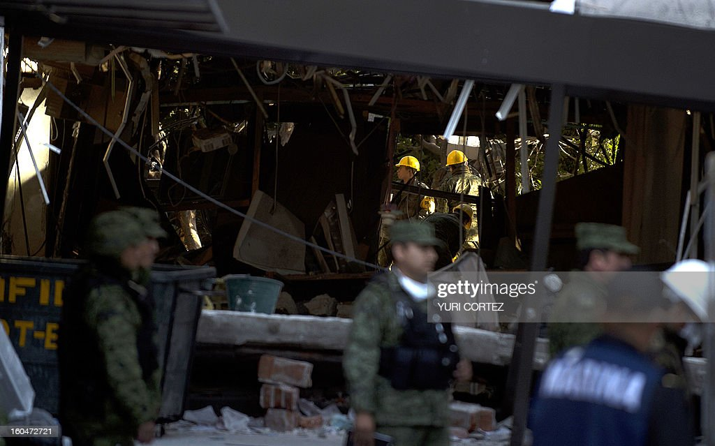 Soldiers, federal policemen and firefighters remove debris from the headquarters of state-owned Mexican oil giant Pemex in Mexico City on February 1, 2013, following a blast inside the building. An explosion rocked the skyscraper, leaving up to now 32 dead and 100 injured, as a plume of black smoke billowed from the 54-floor tower, according to official sources. AFP PHOTO/ YURI CORTEZ
