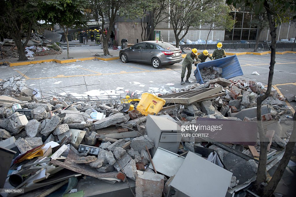 Soldiers, Federal policemen and firefighters remove debris from the headquarters of state-owned Mexican oil giant Pemex in Mexico City on February 1, 2013, following a blast inside the building leaving up to now 32 dead and 100 injured.