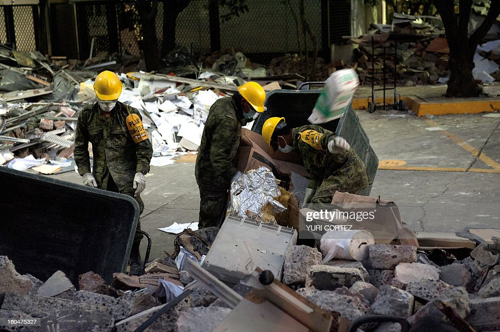 Soldiers, Federal policemen and firefighters remove debris looking for victims in the headquarters of state-owned Mexican oil giant Pemex in Mexico City on February 1, 2013, following a blast inside the building leaving up to now 32 dead and 100 injured. AFP PHOTO/ YURI CORTEZ