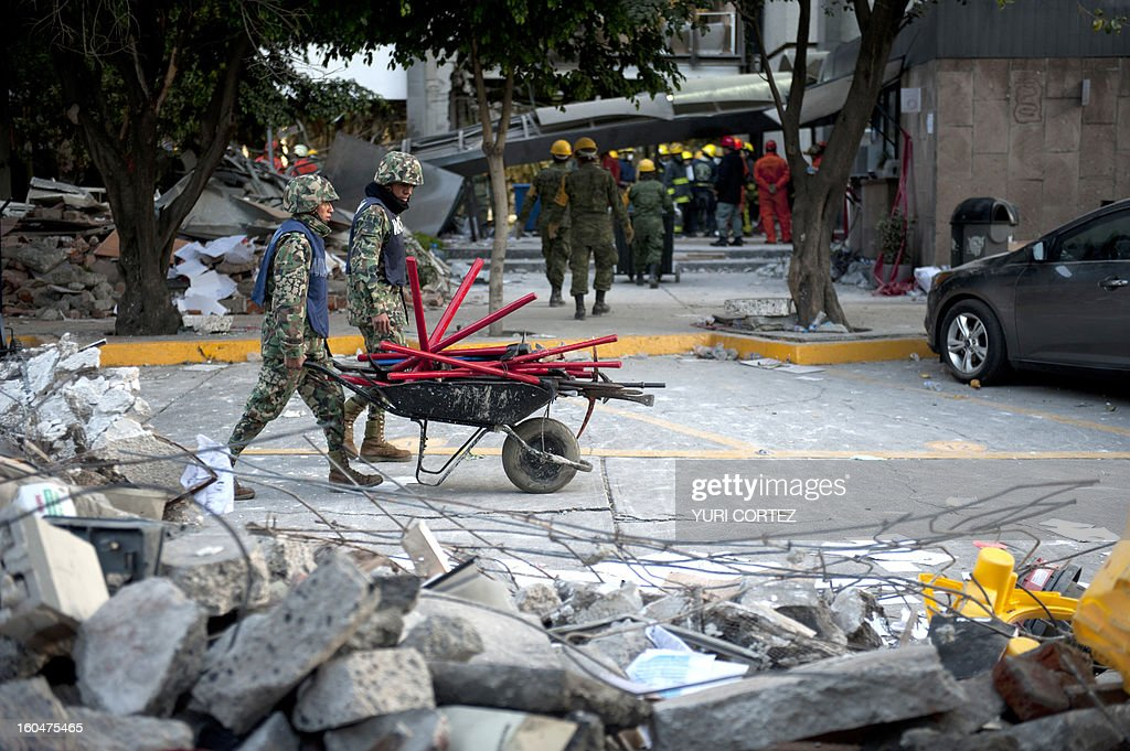 Soldiers, Federal policemen and firefighters remove debris looking for victims in the headquarters of state-owned Mexican oil giant Pemex in Mexico City on February 1, 2013, following a blast inside the building leaving up to now 32 people dead and 100 injured. AFP PHOTO/ YURI CORTEZ
