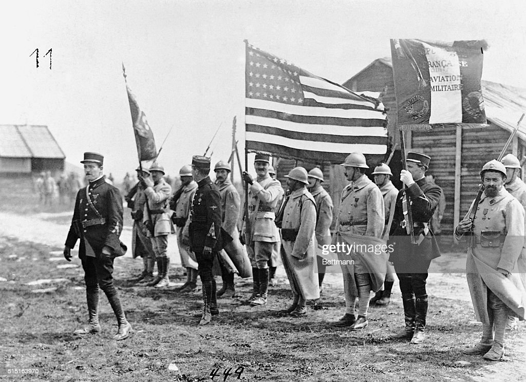 Soldiers flying the American flag which was presented to Lieutenant William Thaw the premier aviator of the Lafayette Esquadrilles as he leads the...