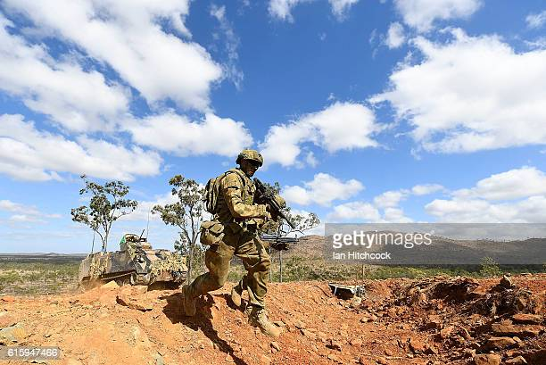 Soldiers from 1 RAR jump into a simulated enemy trench position after completing an assault on the position during the 3rd Brigade Live Fire Exercise...