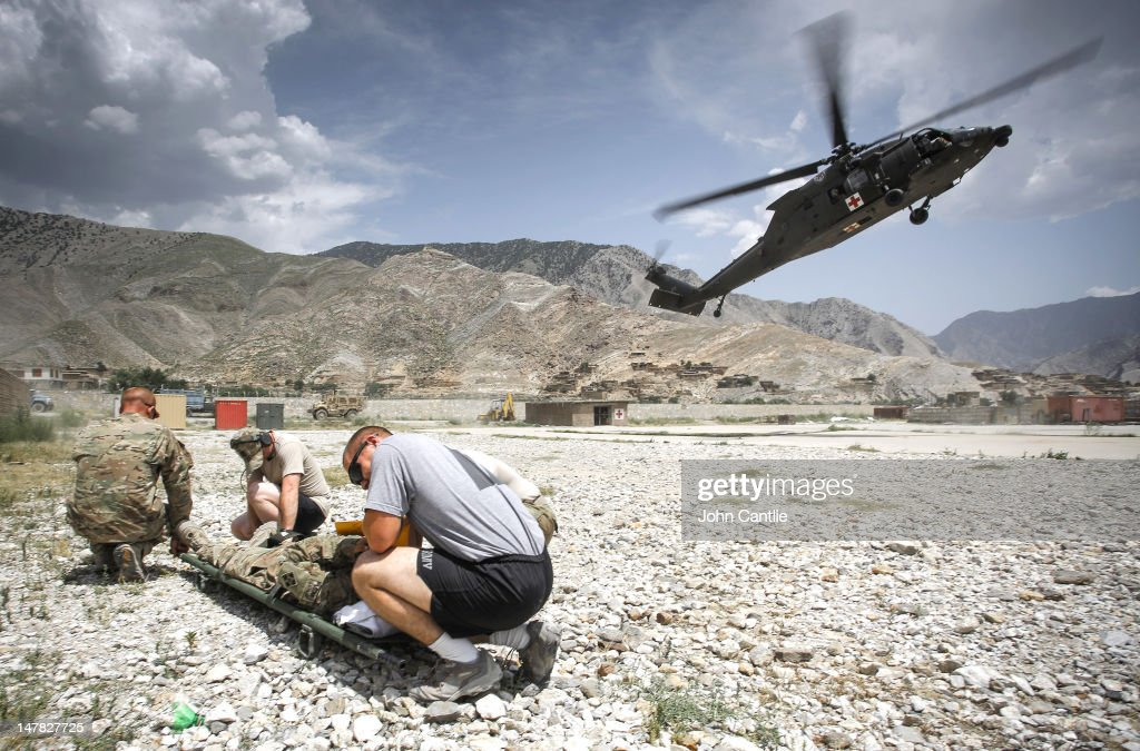 US soldiers from 212 Infantry Regiment out of Colorado Springs shelter from the downdraft of a medevac helicopter as it lands to pick up a casualty...