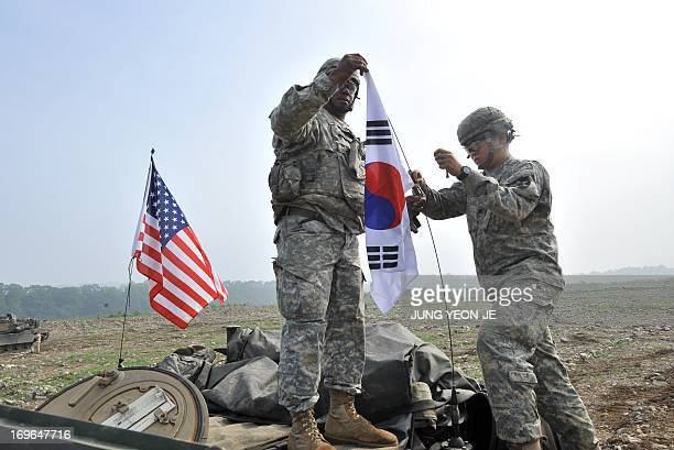 US soldiers from 2nd Infantry Division hang a South Korean flag on the top of their M1A2 tank during a USSouth Korea joint river crossing exercise in...