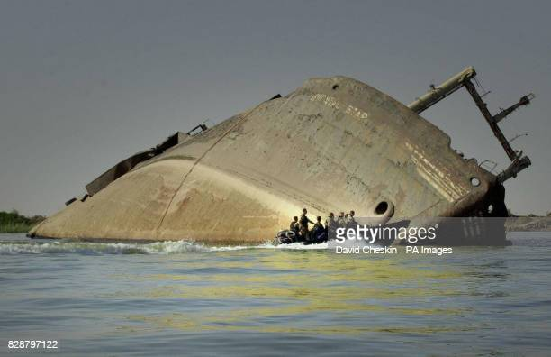 Soldiers from 40 Regiment Royal Artillery and 157 Battery Royal Marines pass a capsized vessel as they patrol the Shatt Al Arab river where coalition...