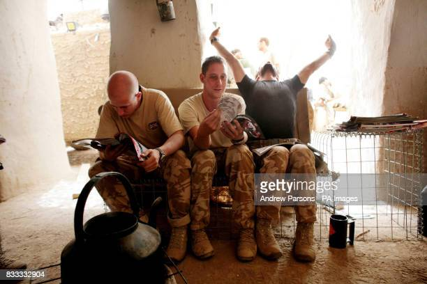 Soldiers from B Company Worcester and Sherwood Forest regiment read a new batch of magazines that have just arrived on base in the Helmand provence...