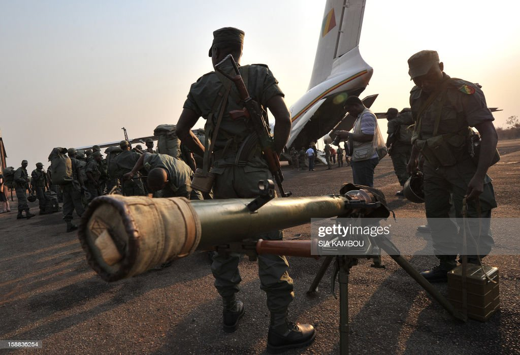 Soldiers from Congo Brazzaville, part of the Multinaional Force of the Economic Community of Central African States (FOMAC), unload military equipment as they arrive at the airport in Bangui, on December 31, 2012. Congo announced today the deployment of a battalion of 120 soldiers to the Central African Republic's capital Bangui at the request of the Tchadian President Idriss Deby, who is currently the president of FOMAC. Meanwhile rebels in the Central African Republic vowed to take the last key town before the capital and renewed their call for the president to stand down, voicing scepticism over his pledge to make concessions. AFP PHOTO / SIA KAMBOU