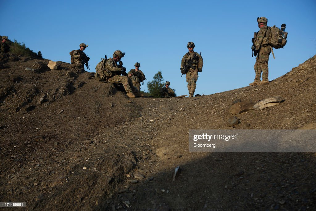 Soldiers from Easy Co. of the 2-506th Infantry Battalion of the 4th Brigade of the 101st Airborne Division conduct a mission with the Afghan National Army and Police in the remote Musa Khel district of Khost province, Afghanistan, on Wednesday, July 3, 2013. U.S. President Barack Obama has maintained his position of ending U.S. combat in Afghanistan by the end of next year, though that plan has included keeping in place several thousand troops for support. Photographer: Victor J. Blue/Bloomberg via Getty Images