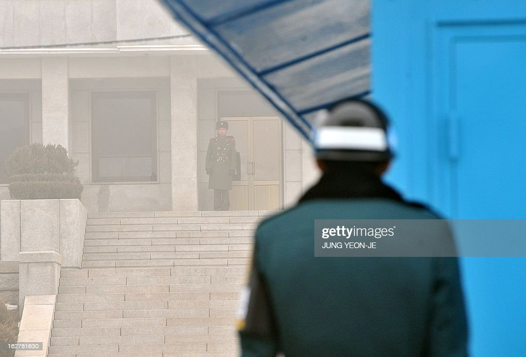 Soldiers from South Korea (R) and North Korea (C back) stand guard on their respective sides at the truce village of Panmunjom in the demilitarized zone dividing North and South Korea on February 27, 2013. North Korean leader Kim Jong-Un oversaw a live-fire artillery drill aimed at simulating an 'actual war', state media said on February 26, a day after South Korea swore in its first female president. AFP PHOTO / JUNG YEON-JE